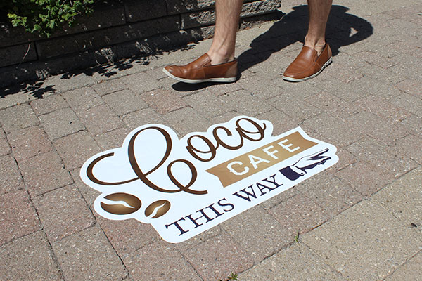 Branded street decal pointing to a coffee shop