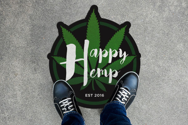 Street decal of a cannabis brand on a sidewalk with a person standing over it