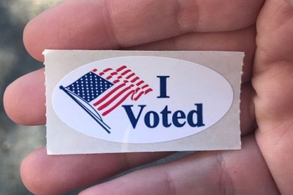 I voted sticker held in a voter's hand
