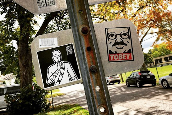 Artist Urban Ninja's stickers on a sign