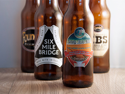 Beer bottles with a variety of custom die-cut beer labels applied to them
