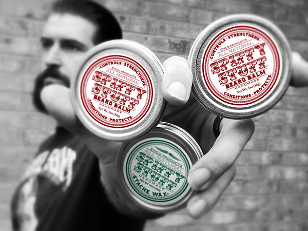 Man holding up beard balm containers with custom labels