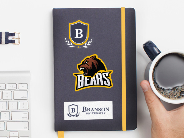Notebook with university sitkcers on it