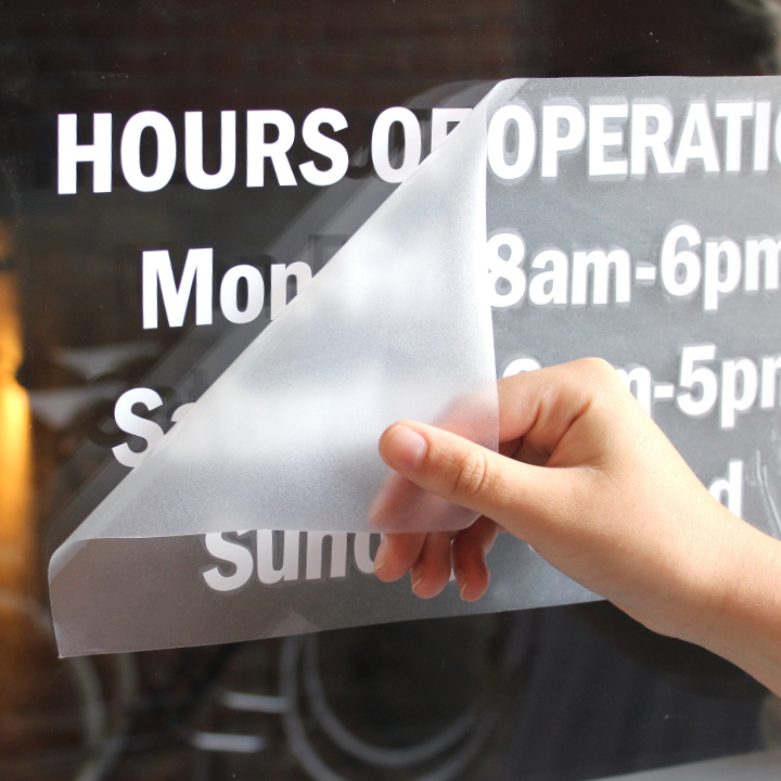 Vinyl lettering and number store hours on a window
