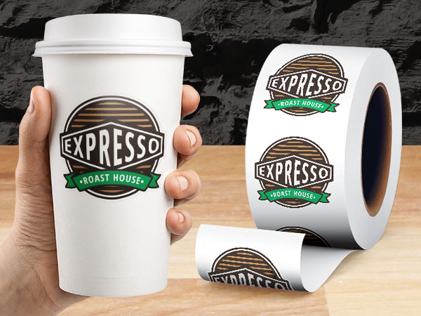 A roll of coffee shop logo stickers and a logo sticker applied to a blank paper