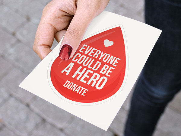 Woman handing out kiss-cut stickers for blood donation