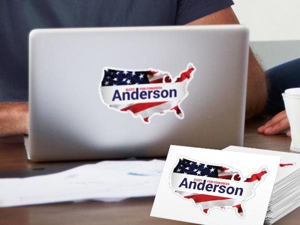 Custom political campaign sticker on a laptop and a stack of kiss-cut stickers next to it